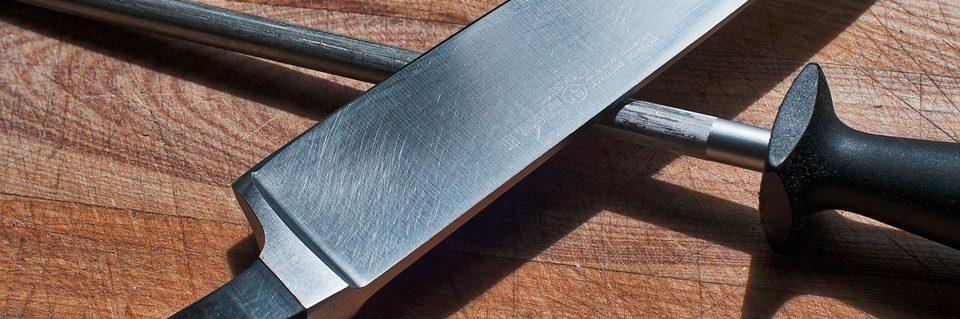 Tabla que presenta un cuchillo y una afilador de cuchillos